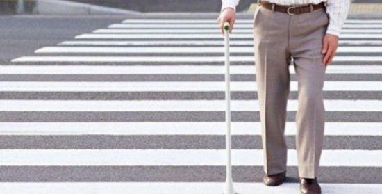 Мужчина с тростью переходит дорогу