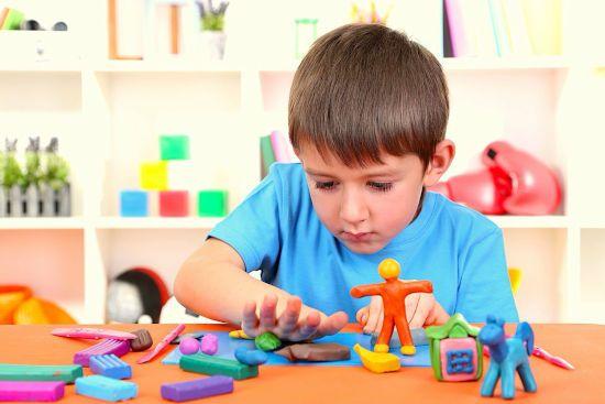Мальчик лепит из пластилина